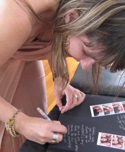 Lady Writing Inside a Dry Mount Photo Album Next To Photo Booth Strip Photos